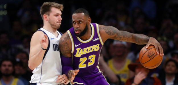 Luka Doncic intenta defender a LeBron James.
